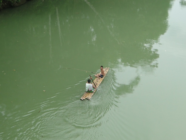 teens fishing in a man-made bamboo raft with bamboo fishing pole